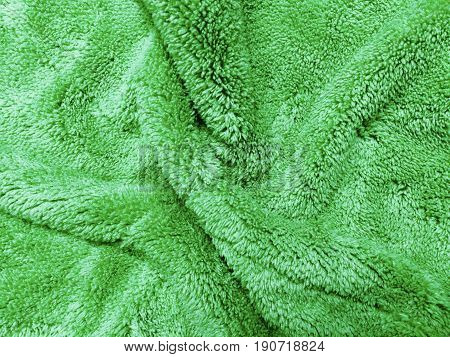 Fabric Texture Close Up of Green Rippled Plush Pattern Background with Copy Space for Text Decoration.