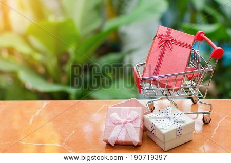 mini supermarket shopping cart with mini colorful gift box on blurred green nature background with sunlight effect holiday sale and online shopping concept selective focus copy space
