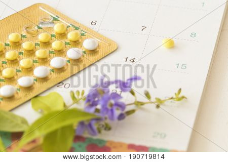birth control pills of baby for woman and calendar on white