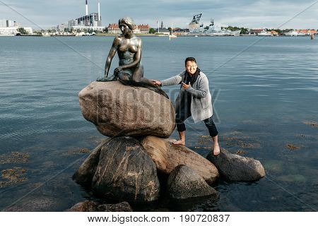 Copenhagen Denmark - August 11 2016: Some unidentified tourists trying to climb to little mermaid statue in Copenhagen Denmark. Evening in summer