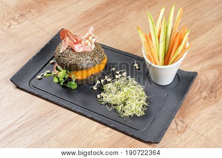Healthy burger with hamon, tomatoes, micro greens and black wholegrain buns, vegetable sticks on black slate board over wooden background. Clean eating, dieting, detox food concept