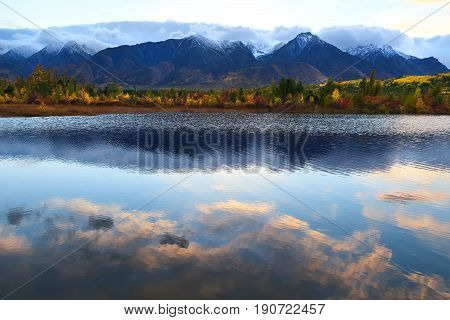 Pink cloud reflections in smooth water surface, colorful forest and mountain peaks capped with snow, autumn landscape on sunset
