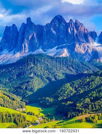 Alpine meadows. Magnificent serrated cliffs, green valley and small village in the Dolomites illuminate the summer sunset. The concept of eco-tourism in Tirol
