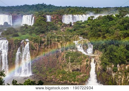 The concept of exotic and extreme tourism. Powerful waterfalls Iguazu - a recognized miracle of the world. Powerful two-stage waterfalsl creates watery dust and rainbow