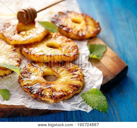 Grilled pineapple slices with addition of honey on a blue table
