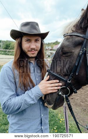 Young Man With Long Hair In Hat Holding Horse's Muzzle On Countryside And Looking At Camera