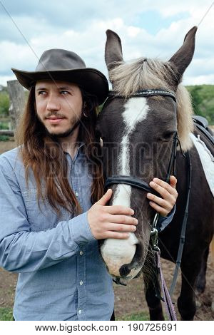Young Man With Long Hair In Hat Holding Horse's Muzzle On Countryside And Looks Into The Distance