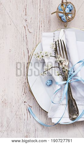 Vintage easter table setting with eggs spring blossoms and silverware on a old white wooden board. Copy space. Top view.