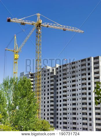 Two different tower cranes with latticed booms on a construction of a multi-story residential building and trees in the foreground