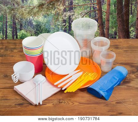 Different disposable plastic and paper cutlery paper napkins and roll of disposable garbage bags on the old wooden planks against the background of the pine forest