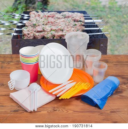 Different disposable plastic and paper cutlery paper napkins and roll of disposable garbage bags on the old wooden planks against the background of barbecue grill with grilled skewered meat outdoors