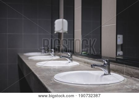 Faucets with white washbasin in public restroom