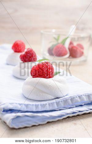 Pavlova - mini meringue cake with raspberries copy space close up selective focus.