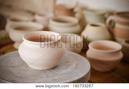 many clay pot is on the table in pottery. Copy spase