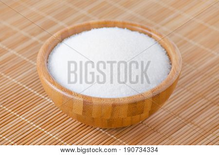 a wooden bowl with whte sugar on bamboo texture selective focus