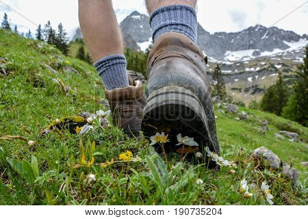 Hiking in the mountains with brown hiking boots and sticks