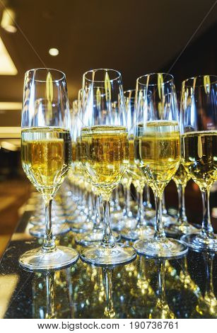 Several glasses of champagne bartender prepared for guests of festive events. Catering during events and holidays. Festive champagne in glasses.
