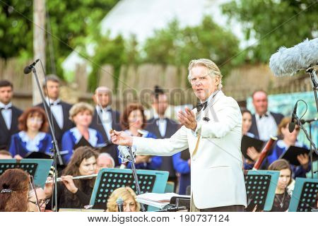 ORHEIUL VECHI, MOLDOVA - JUNE 08, 2017: Conductor Friedrich Pfeiffer performing at Descopera Butuceni Village open air music festival, symphonic orchestra of Moldova