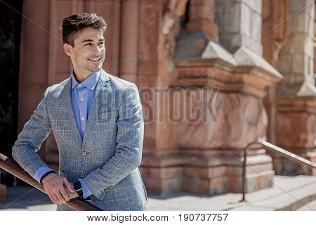 Cheerful man is standing near iron banisters and turning his head. He looking with smile. Copy space