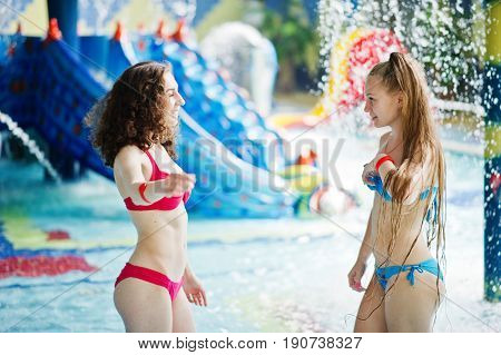 Two Fantastic Girls Posing In The Pool In The Water Park Wearing Red And Blue Swimsuit.