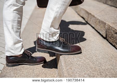 Stylish man is standing on rungs. Close up of legs in polished shoes