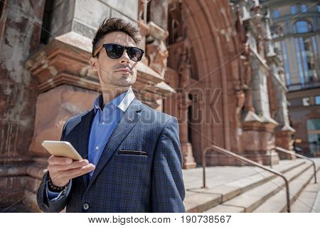 Thoughtful man is holding phone and looking ahead with confident glance. He wearing sunglasses