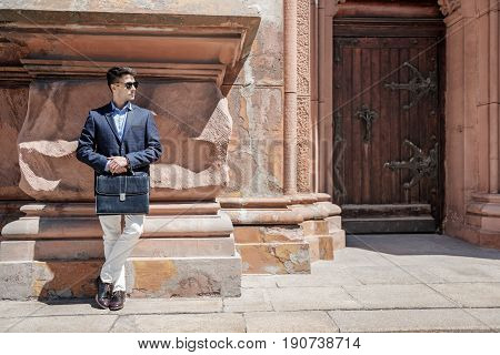Confident man wearing sunglasses is leaning against wall and holding case. He looking aside. Copy space on right side