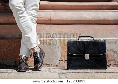 Elegant man is standing near wall. Black leather case locating near legs in polished oxfords. Close up