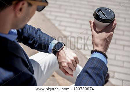 Stylish busy male person is holding beverage and looking at modern wristwatch. Top view