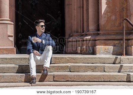 Cheerful man sitting on stairs and holding beverage. He wearing sunglasses is looking aside