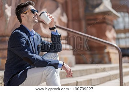 Hilarious male person wearing sunglasses is holding cup of beverage and going to drink it. He looking up with smile