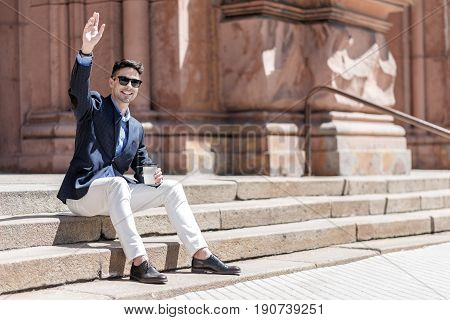 Happy businessman is waving hand and looking ahead with smile. He sitting outside on stairs. Copy space on right side