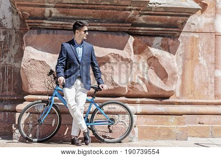 Confident man is leaning against blue bicycle. He wearing sunglasses and looking aside with light smile. Copy space on right side