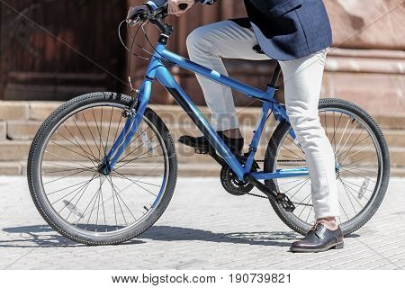 Well dressed man is getting on bicycle and going to start. Focus on two-wheeled transport. Close up