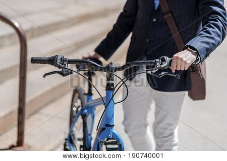 Fashionable man is standing near bike and putting hand on handlebar. He going to ride two-wheeled transport. Close up