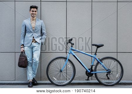 Cheerful man is leaning against wall and looking at camera with smile. He standing near blue modern bicycle. Portrait