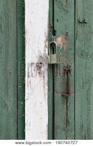 Closeup of old wooden boathouse door background with hook and padlock, in Finland.