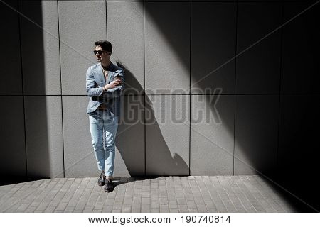 Assured man is leaning against wall and looking aside with light smile. He holding beverage. Copy space on right side