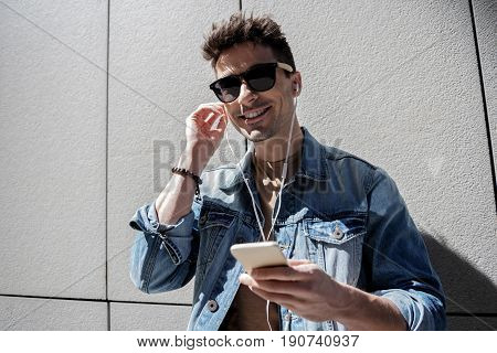 Hilarious man wearing sunglasses is leaning against wall and listening to music from earphones. He looking ahead with bright smile. Portrait