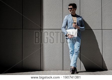 Cheerful man wearing sunglasses is leaning against grey wall and looking aside with smile. He holding laptop. Copy space on left side