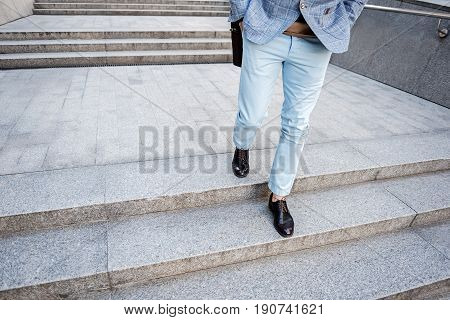 Elegant man is going down stairs outside. Focus on close up his legs wearing leather oxfords. Copy space on left side