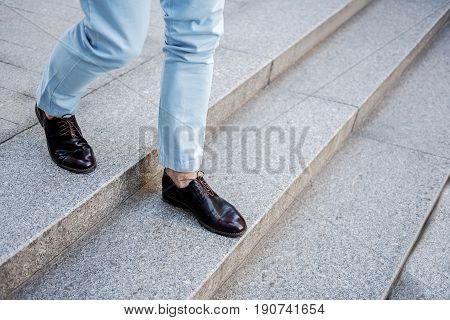 Fashionable man is walking downstairs. Close up of leather shiny shoes on foot
