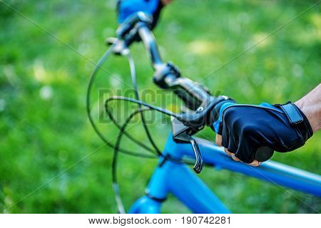 Close up of male hands on handlebars of bicycle. Arms in special protective gloves