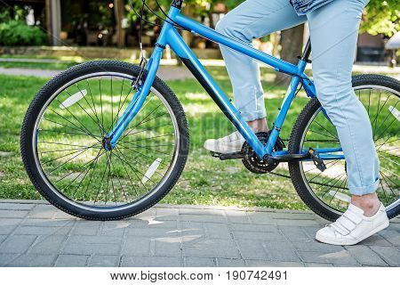 Sporty man is getting on bicycle and ready to ride. Focus on two-wheeled transport. Close up