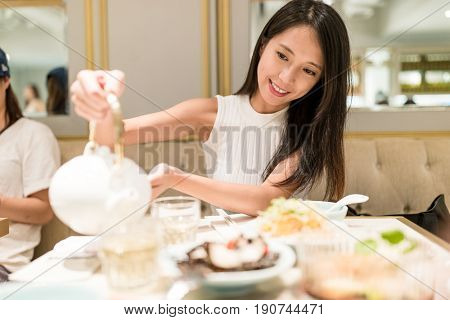 Young woman pouring chinese tea in restaurant