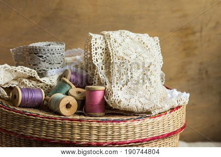 Wooden spools of multi color threads rolls of beige and grey cotton lace on sewing rattan wicker basket hobby crafts concept copy space