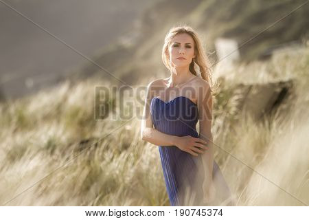 outdoor portrait of young beautiful blonde woman in blue gown posing on natural background