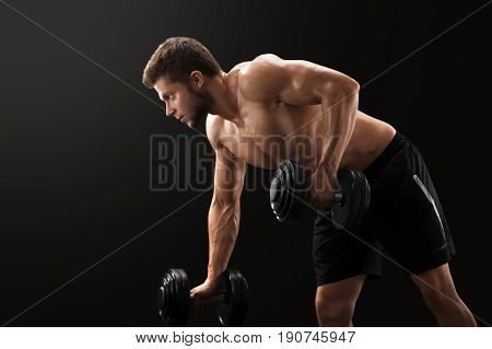 Horizontal studio shot of a young muscular handsome sportsman lifting weights exercising on black background sport lifestyle strength masculinity athletics sexy shirtless power endurance bodybuilding.