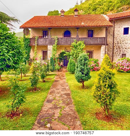 Idyllic stone rural house with pretty cottage garden. Square image