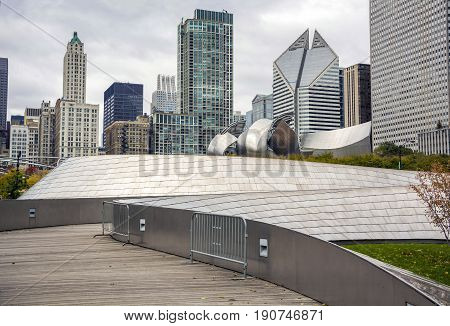 Chicago IL USA october 27 2016: The BP Bridge in Millennium Park Chicago Illinois USA Chicago skyline in the background cloudy day